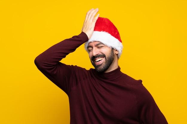 Un homme avec un chapeau de noël sur un mur jaune isolé a réalisé quelque chose et visait la solution