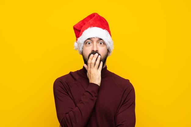 Homme avec chapeau de noël sur mur jaune isolé surpris et choqué tout en regardant à droite