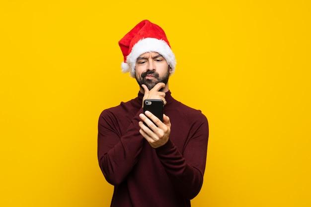 Homme avec chapeau de noël pensant et envoyant un message
