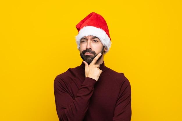 Homme avec un chapeau de noël sur la pensée de mur jaune isolé