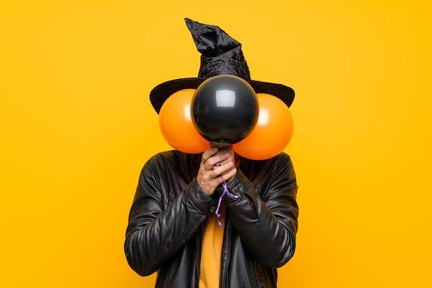 Homme avec chapeau de sorcière tenant des ballons à air noir et orange pour la fête d'halloween couvrant les yeux par la main