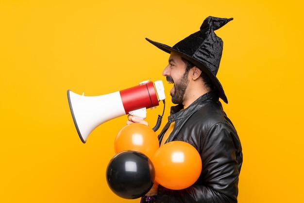 Homme avec chapeau de sorcière tenant des ballons à air noir et orange pour la fête d'halloween criant à travers un mégaphone