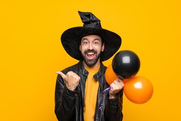 Homme avec chapeau de sorcière tenant des ballons à air noir et orange pour la fête d'halloween avec le geste du pouce en l'air et souriant
