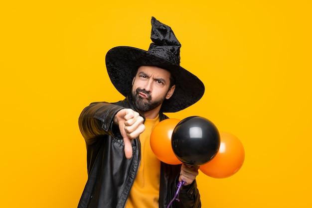 Homme avec chapeau de sorcière tenant des ballons à air noir et orange pour la fête d'halloween montrant le pouce vers le bas avec une expression négative