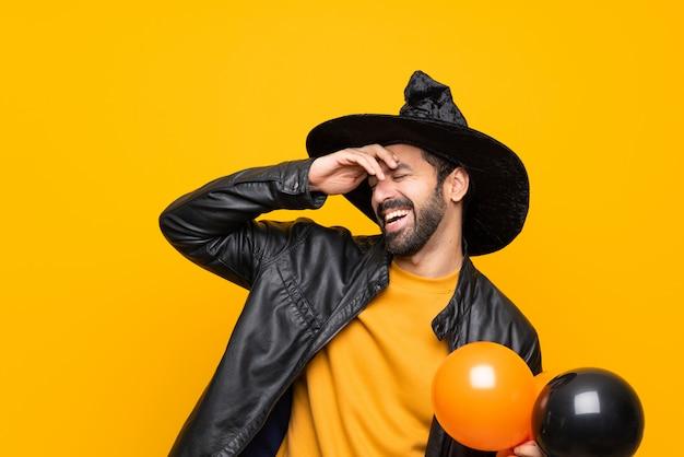 Homme avec chapeau de sorcière tenant des ballons à air noir et orange pour la fête d'halloween a réalisé quelque chose et dans l'intention de la solution