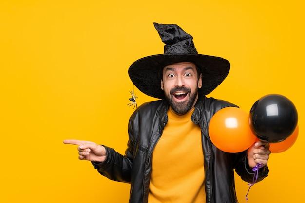 Homme avec chapeau de sorcière tenant des ballons à air noir et orange pour la fête d'halloween surpris et un doigt pointé sur le côté
