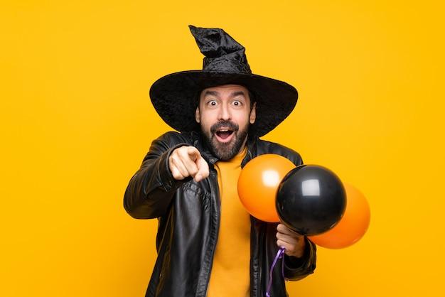 Homme avec chapeau de sorcière tenant des ballons à air noir et orange pour la fête d'halloween surprise et pointant le devant