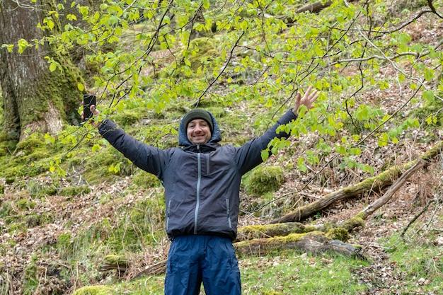 Homme avec chapeau souriant levant les bras en forêt