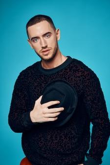 Homme à chapeaux de chandail noir posant fond bleu studio de mode