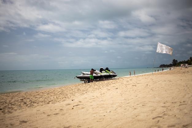 L'homme charge sur un chariot jet skis sur une plage de sable sur fond de mer avec des vagues un drapeau blanc