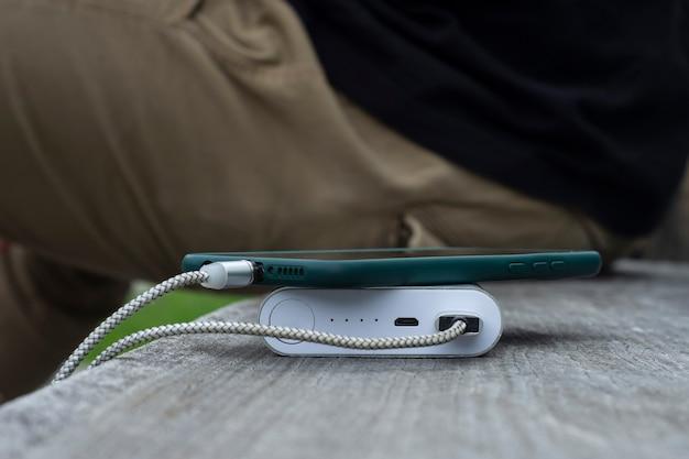 Un homme charge un smartphone avec une banque d'alimentation sur un banc en bois.