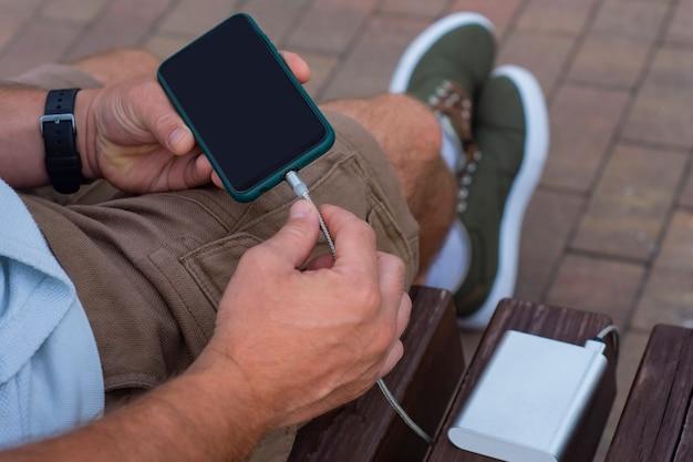L'homme charge un smartphone avec une banque d'alimentation à la main. chargeur portable pour charger des gadgets.