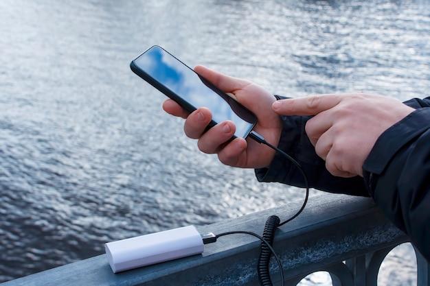 Un Homme Charge Un Smartphone Avec Une Banque D'alimentation. Le Téléphone En Main Est En Train D'être Chargé Avec Un Chargeur Portable Dans Le Contexte Du Lac. Photo Premium