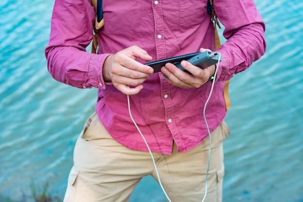 L'homme charge un smartphone avec un chargeur portable. un homme avec une banque d'alimentation à la main sur le fond de la mer par une belle journée ensoleillée avec des nuages.