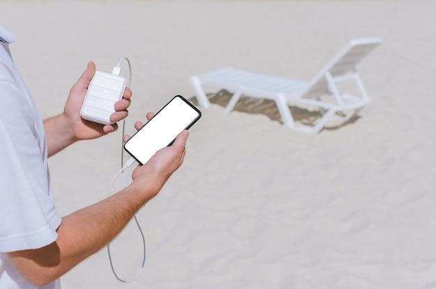 Un homme charge un smartphone à partir d'une banque d'alimentation sur la plage. sur fond de sable et de transat blanc.