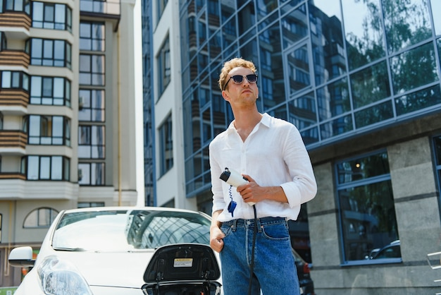 Homme chargeant sa voiture électrique de luxe à la station extérieure devant les nouveaux bâtiments modernes de la ville