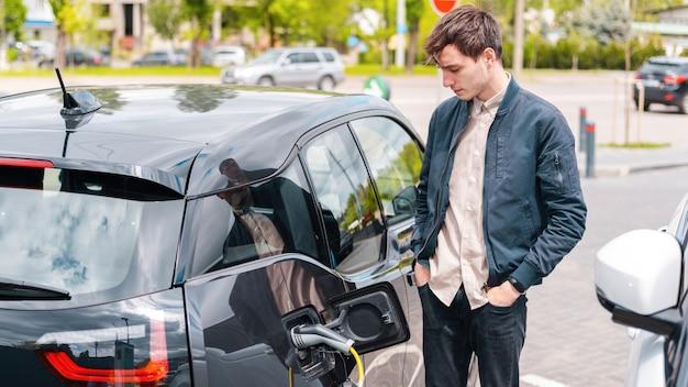 Homme chargeant sa voiture électrique à la station de charge