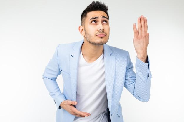 Homme charmant dans une veste classique bleue pense à la discussion et au problème sur un fond blanc avec espace de copie.