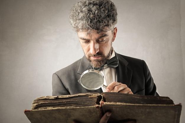 Homme charmant à la recherche avec une loupe