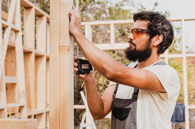 Homme charpentier à l'aide d'un ruban à mesurer
