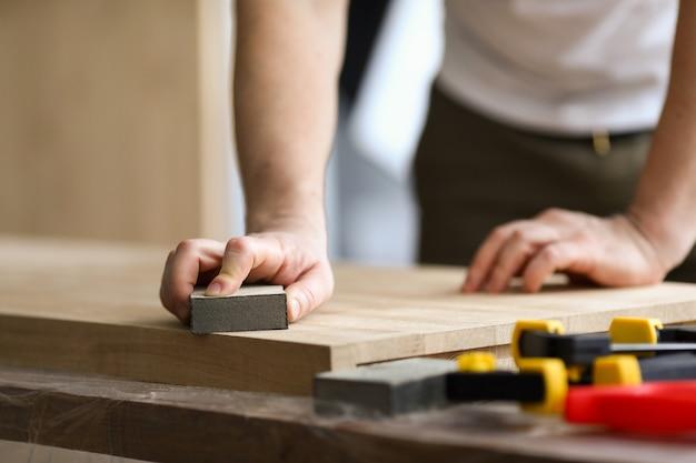 Homme charpentier broie une feuille de bois en atelier. le menuisier de lieu de travail est équipé d'un établi sur lequel il était pratique d'effectuer des travaux sur la fabrication de pièces de mobilier. principales méthodes de transformation du bois