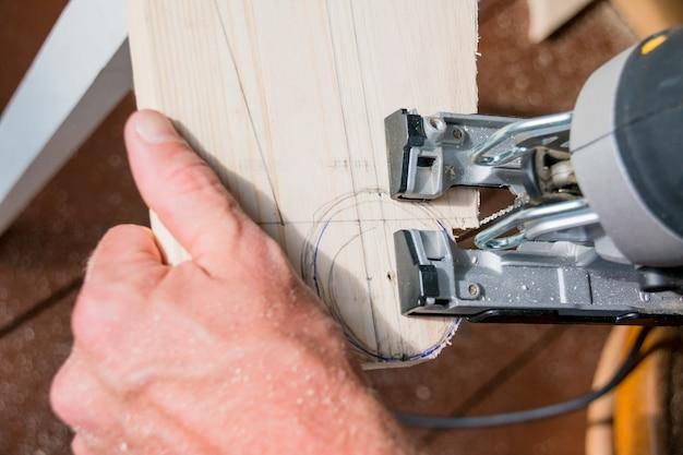 Homme charpentier constructeur travaillant avec puzzle électrique et wood.hobby concept