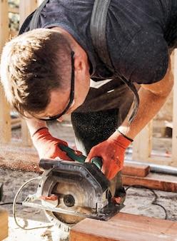 Homme charpentier coupe une planche de bois vue haute