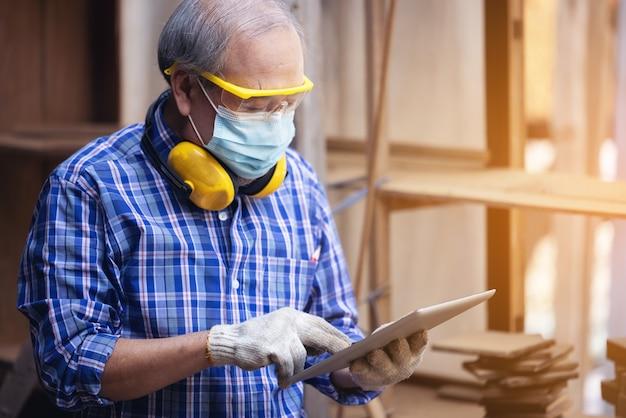 Homme charpentier dans un atelier de construction, à l'aide d'une tablette numérique