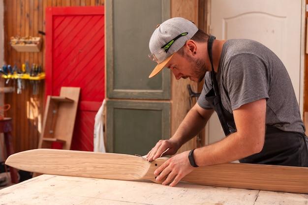Un homme charpentier dans une casquette, des lunettes et un tshirt ponce un bois dans l'atelier
