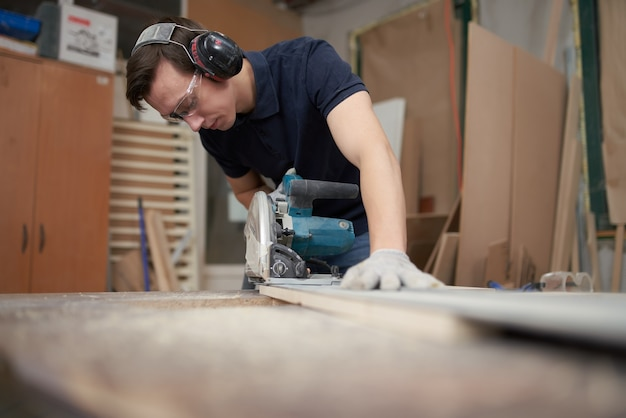 L'homme de charpentier dans les écouteurs protecteurs et les gants blancs travaille sur le puzzle dans l'atelier