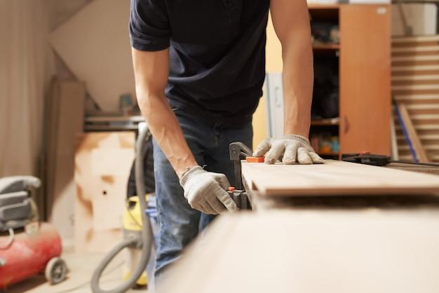 L'homme charpentier en gants pinces conseil en vice à l'atelier