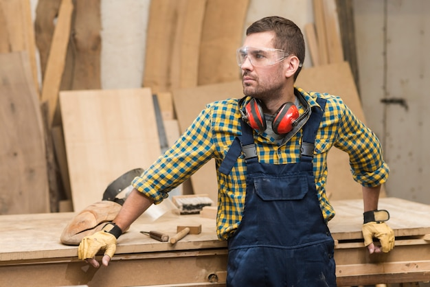 Homme charpentier avec lunettes de sécurité et protège-oreilles autour du cou, debout devant un établi en bois