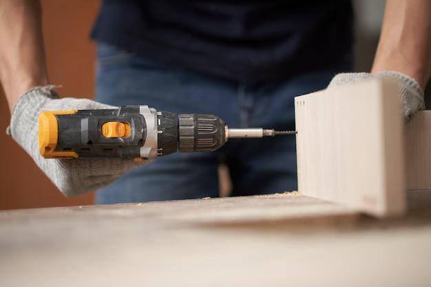 Homme de charpentier méconnaissable en gants blancs avec perceuse et planche en atelier