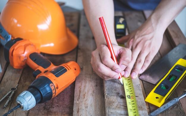 Homme charpentier mesure sur bois avec un crayon.