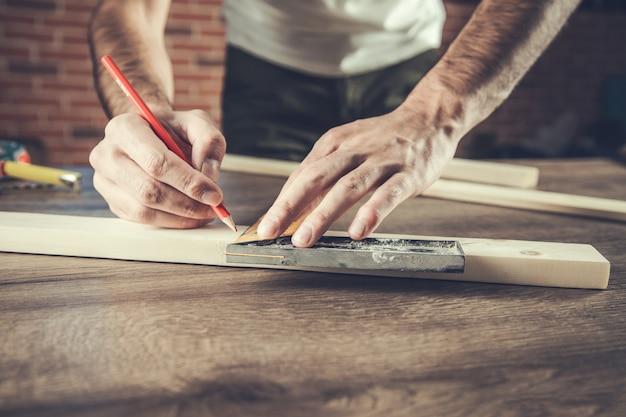 L'homme charpentier mesure la planche de bois