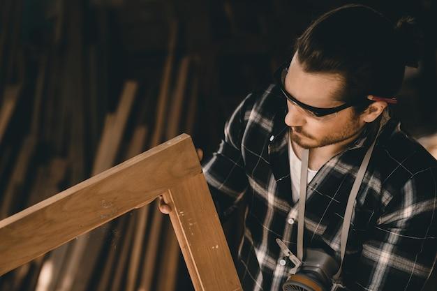 Homme charpentier professionnel qualifié dans le travail du bois à la recherche de détail de chef-d'œuvre de l'artisanat du bois dans l'atelier de meubles