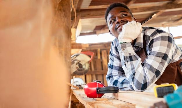 L'homme de charpentier rêve de son propre logement au chantier