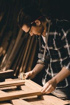 Homme charpentier s'occuper de la fabrication de meubles artisanaux de boiseries de chef-d'œuvre sur mesure fine dans l'atelier du bois, prise de vue verticale.