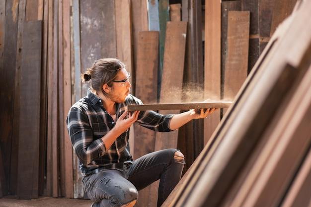 Homme de charpentier soufflant de la sciure sur une planche en bois pour choisir de fabriquer des meubles à l'atelier de menuiserie