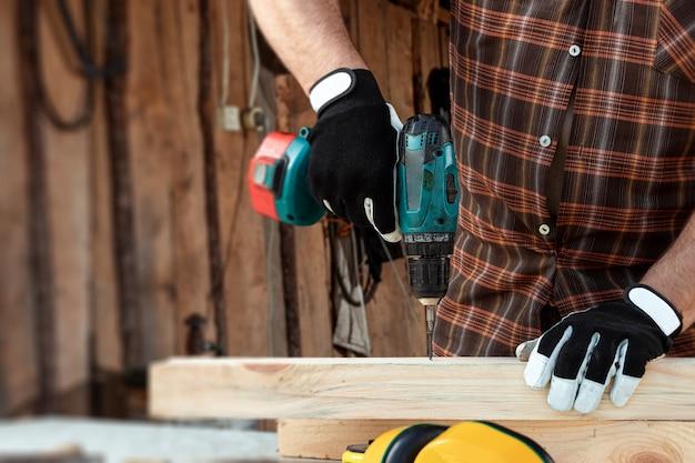 Un homme charpentier tord une vis dans un arbre avec un tournevis électrique, les mains d'un homme avec un gros plan de tournevis.