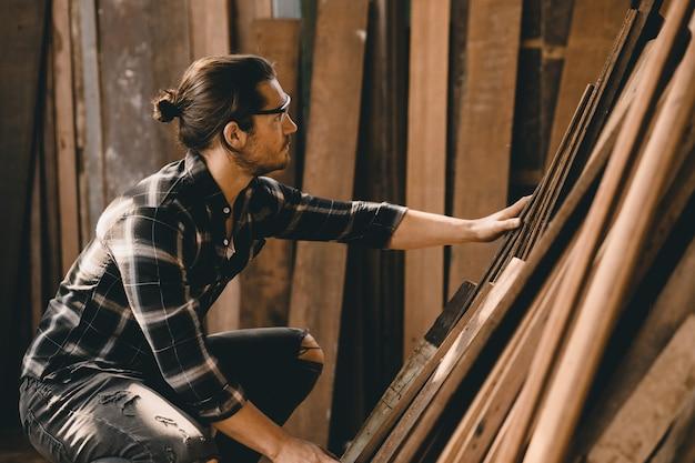 Homme charpentier travaillant dans l'atelier de bois de meubles, sélection de planche de bois.