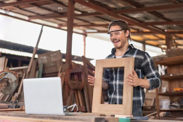 Homme charpentier vendant des châssis de fenêtre en bois en ligne à l'atelier de menuiserie.