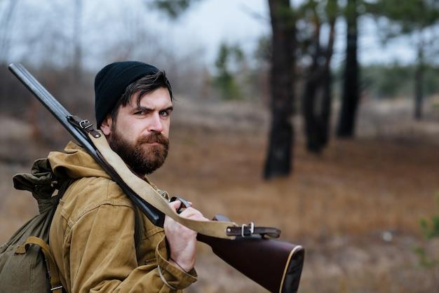 Un homme chasseur avec une barbe et une moustache dans un chapeau noir et un grand sac à dos de randonnée détient une arme à feu sur son épaule en forêt