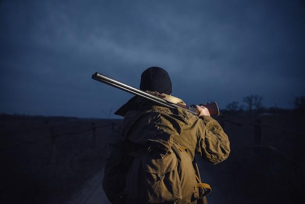 Un homme chasseur dans un chapeau chaud et une veste kaki avec un grand sac à dos sur le dos et un pistolet sur ses épaules