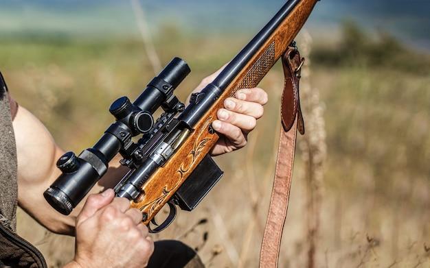 Homme chasseur. période de chasse. homme avec une arme à feu, un fusil. l'homme charge un fusil de chasse. processus de chasse pendant la saison de chasse. chasseur mâle prêt à chasser. fermer. l'homme est à la chasse, sport.