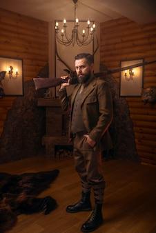 Homme de chasseur respectable dans des vêtements de chasse élégants vintage avec fusil antique contre cheminée.