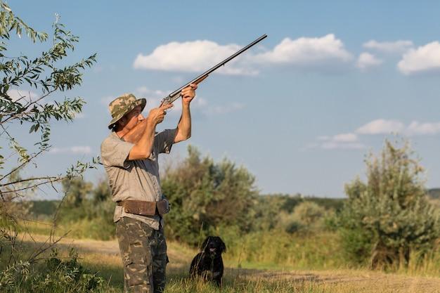 Homme chasseur en tenue de camouflage avec une arme à feu pendant la chasse à la recherche d'oiseaux sauvages ou de gibier. saison de chasse d'automne.