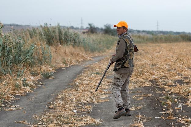 Homme chasseur en tenue de camouflage avec une arme à feu pendant la chasse à la recherche d'oiseaux sauvages ou de gibier