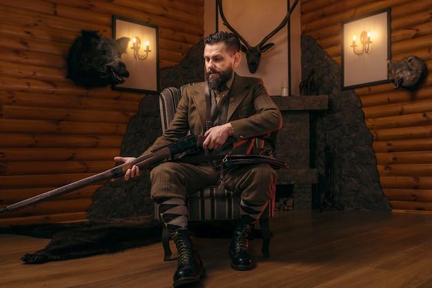 Homme chasseur en vêtements de chasse vintage assis sur une chaise avec fusil antique.