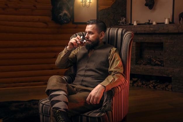 Homme chasseur en vêtements de chasse vintage traditionnels boivent de l'alcool de luxe après une chasse réussie